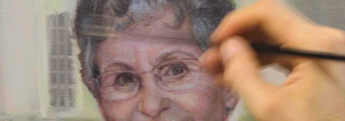 artist's hand paints details on the face of a portrait subject, Bobbie Bailey