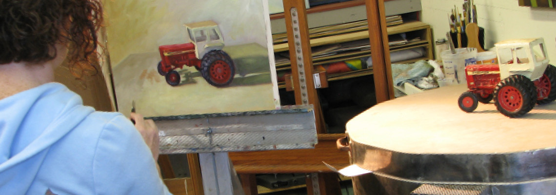Woman paints toy tractor in painting class at Shane McDonald Studios