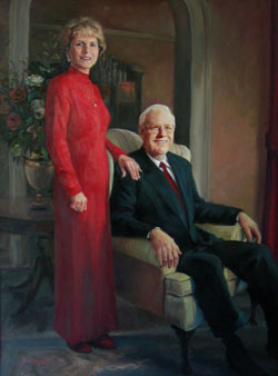 portrait of a standing woman wearing red and a seated man