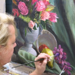 a blonde woman paints a still-life with roses